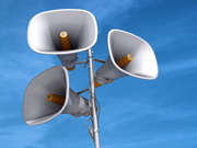 A few megaphones on a pole with a blue sky background.